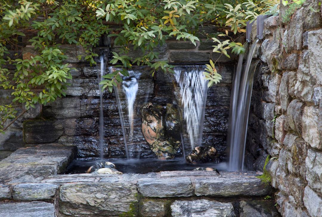 Cascatas de Água AO Longo de hum Rosto de pedra esculpidos no Garden Ruin.  <h6> Photo by Lisa Roper </ h6>